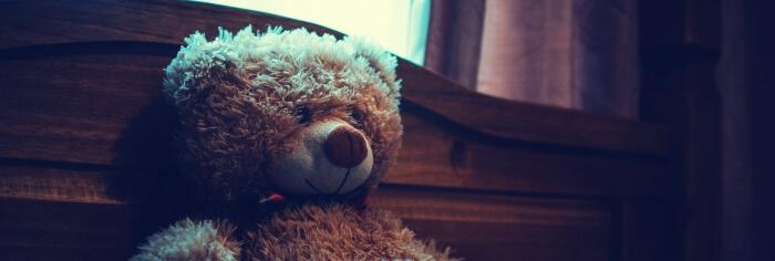 sad teddy bear in bed